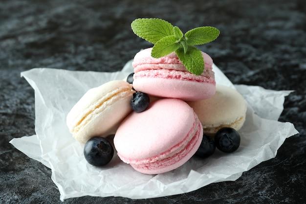 Концепция вкусного десерта с миндальным печеньем на черном дымчатом фоне