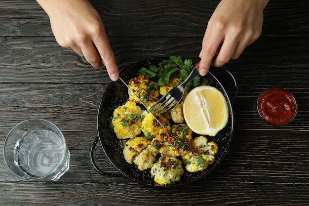 Концепция вкусной еды с запеченной цветной капустой на деревянных фоне.