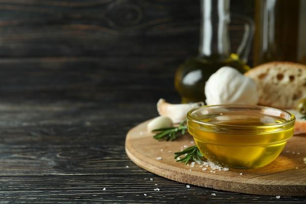 木製のテーブルにオリーブオイルのボウルでおいしい食事の概念