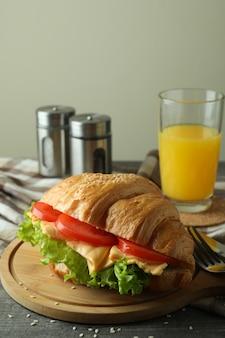 灰色のテクスチャテーブルにクロワッサンサンドイッチでおいしい食事のコンセプト