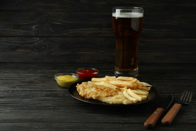 Концепция вкусной еды с жареными чипсами и рыбой и пивом на деревянных