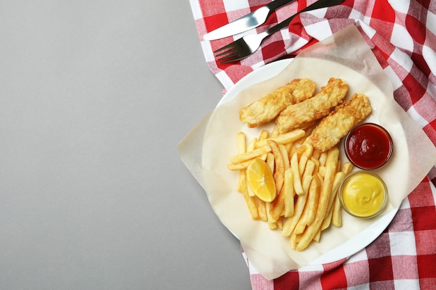 Концепция вкусной еды с жареной рыбой и жареным картофелем на сером фоне