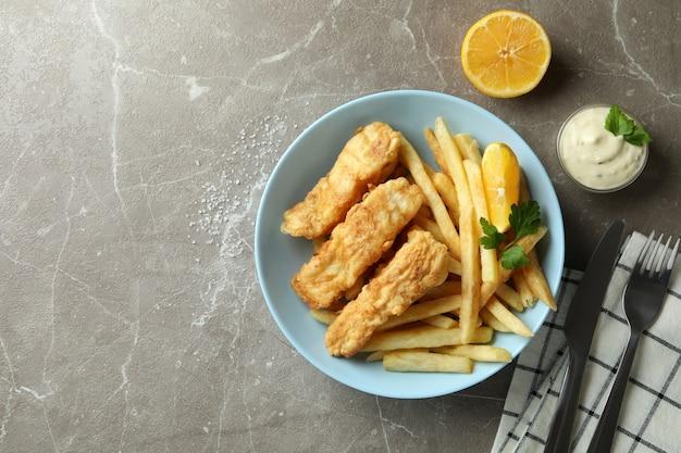 Концепция вкусной еды с жареной рыбой и жареной картошкой на сером текстурированном столе