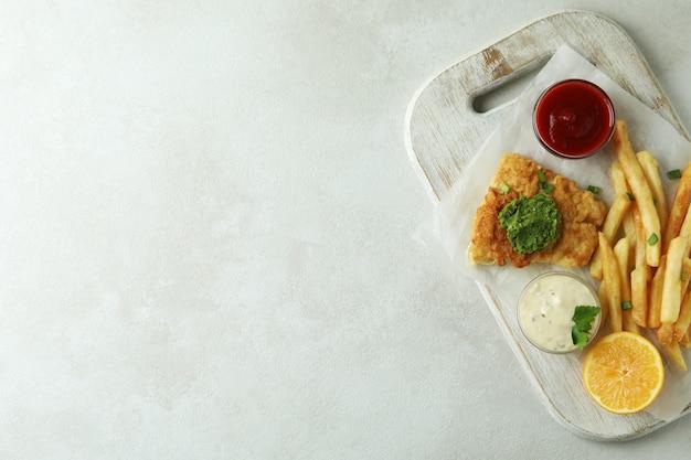 Концепция вкусной еды с жареной рыбой и жареным картофелем на белом текстурированном фоне