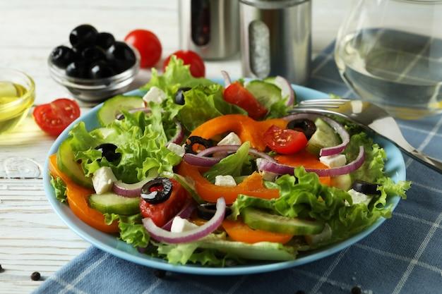 白い木製のテーブルにギリシャ風サラダとおいしい食事の概念