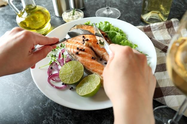 검은 스모키 테이블에 구운 연어와 함께 맛있는 식사의 개념