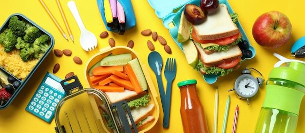 Концепция вкусной еды с ланч-боксами на желтом фоне