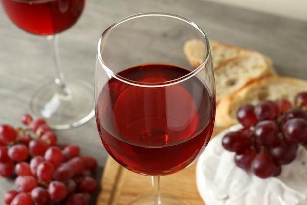 灰色の織り目加工のテーブルで赤ワインとおいしい食事の概念
