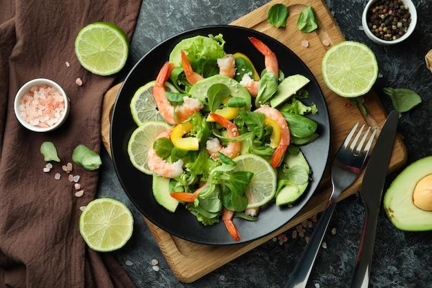 黒のスモーキーな背景にエビのサラダと一緒においしい食事のコンセプト
