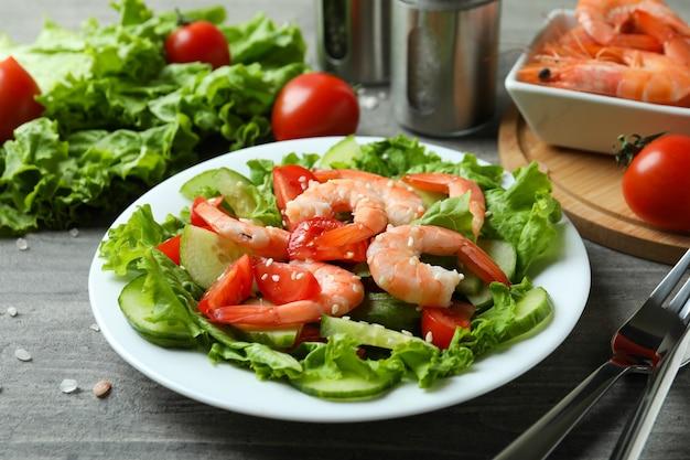 グレーの木製テーブルにエビのサラダを添えておいしい食事のコンセプト