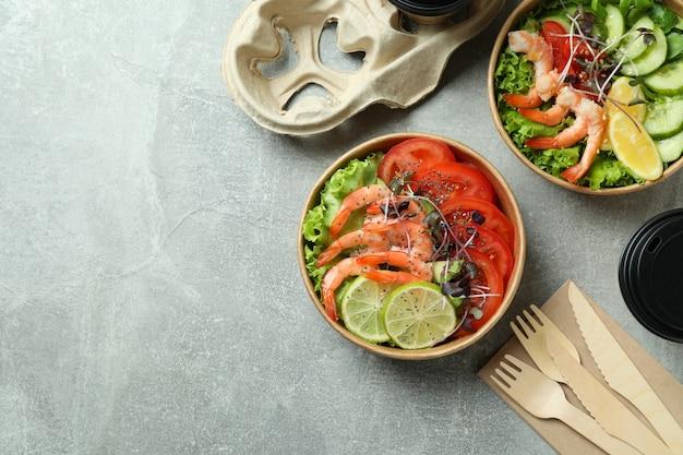グレーのテーブルにエビのサラダを添えたおいしい食事のコンセプト