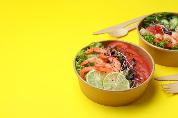 黄色の背景にエビのサラダと一緒においしい食事のコンセプト