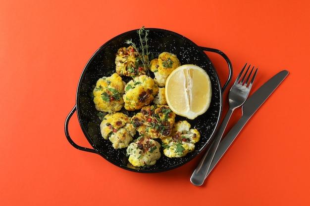 오렌지 배경에 구운 콜리플라워를 곁들인 맛있는 음식의 개념.