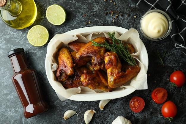 검은 연기가 자욱한 테이블에 구운 닭 날개와 맛있는 음식의 개념
