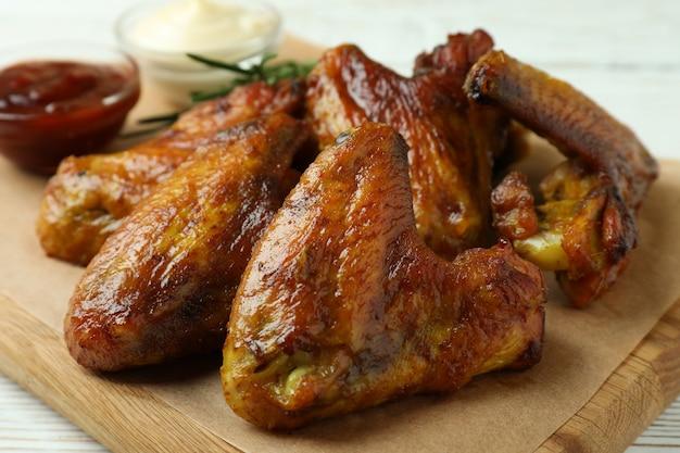 Концепция вкусной еды с запеченными куриными крылышками на белом деревянном