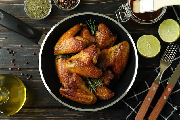 나무 배경에 구운 닭 날개와 맛있는 음식의 개념