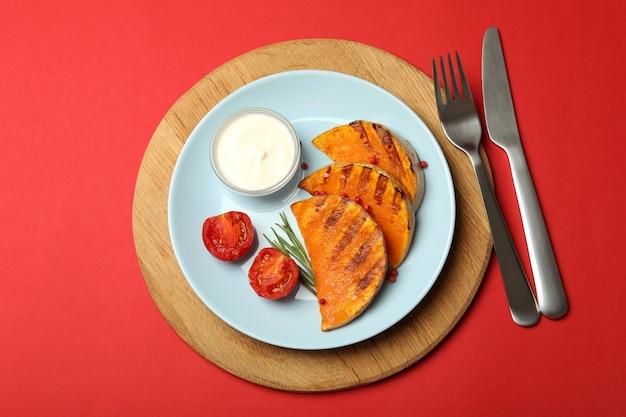 Концепция вкусной еды с запеченной тыквой на красном фоне.