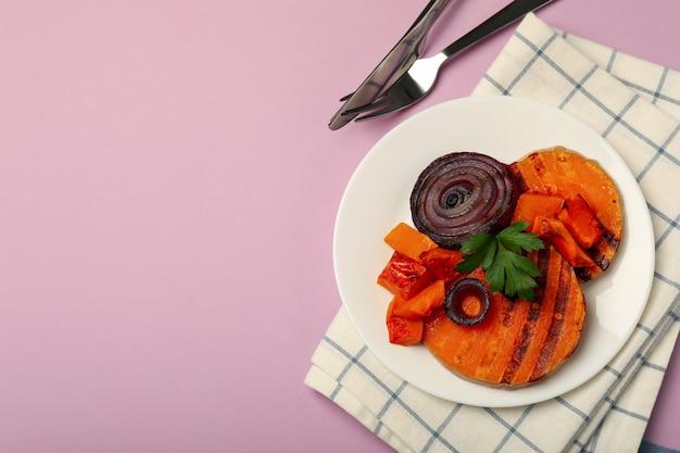Концепция вкусной еды с запеченной тыквой на фиолетовом фоне.