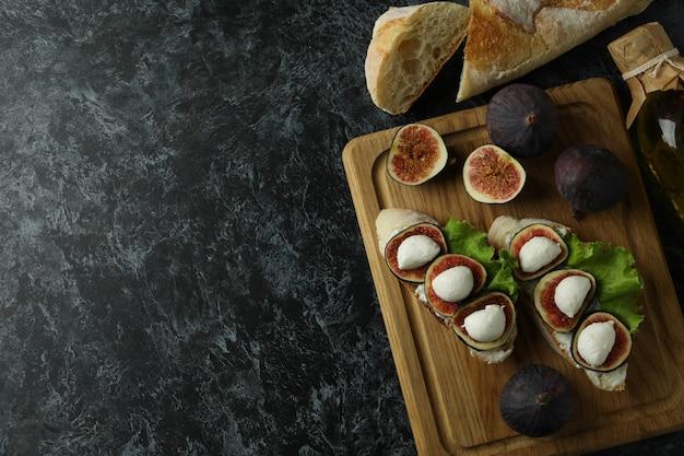 Концепция вкусной еды с брускеттой с инжиром на черном дымчатом столе