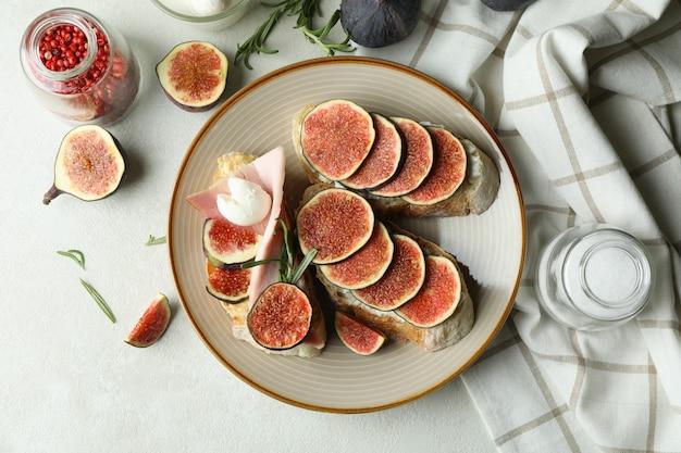Концепция вкусной еды с брускеттой с инжиром на белом текстурированном столе
