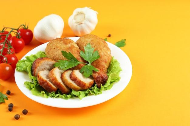 Концепция вкусной еды с котлетами на оранжевом фоне