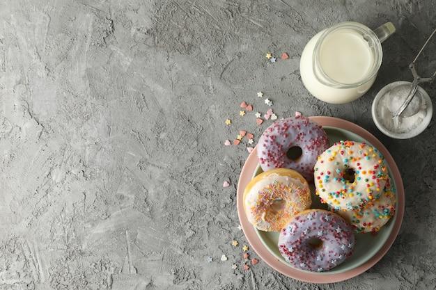 Концепция вкусной еды с пончиками и молоком на сером фоне