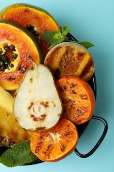파란색 배경에 구운 과일을 곁들인 맛있는 음식의 개념.
