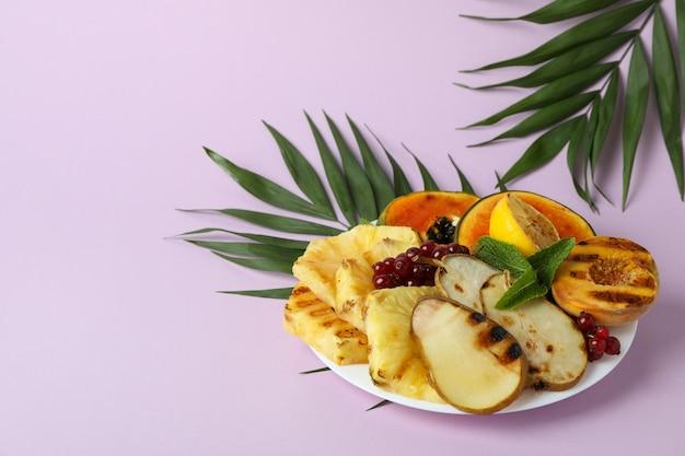 보라색 배경에 구운 과일을 곁들인 맛있는 음식의 개념.