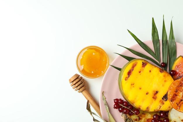 흰색 바탕에 구운 과일을 곁들인 맛있는 음식의 개념.