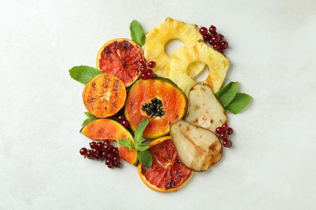 흰색 질감의 배경에 구운 과일을 곁들인 맛있는 음식의 개념.