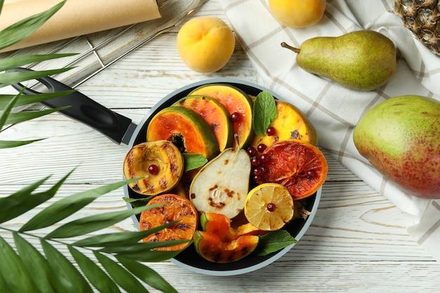 흰색 나무 테이블에 구운 과일을 곁들인 맛있는 음식의 개념.