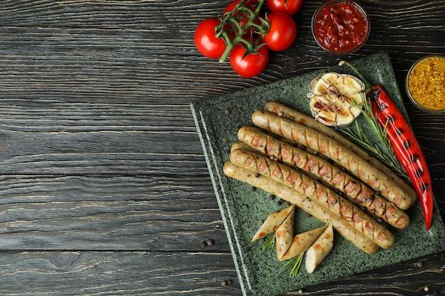 Концепция вкусной еды с жареной колбасой на деревянном столе