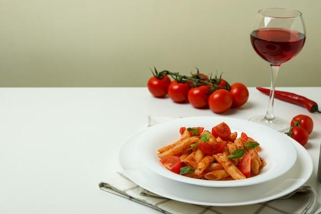 白いテーブルの上にトマトソースのパスタとおいしい料理のコンセプト