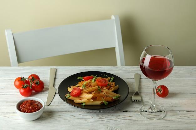 白い木製のテーブルにトマトソースのパスタとおいしい料理のコンセプト