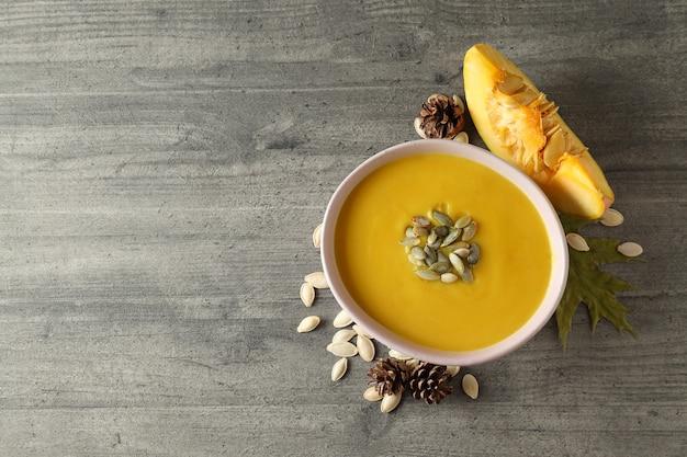 灰色のテクスチャテーブルにカボチャのスープとおいしい料理の概念