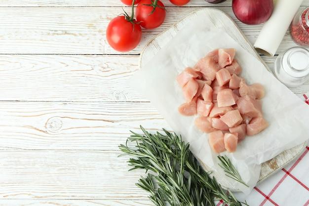 白い木製の背景に生の鶏の切り身のスライスとおいしい料理の概念