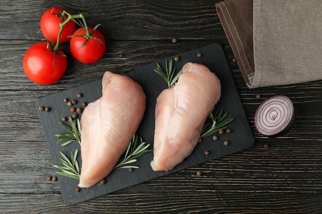 木製の背景に生の鶏の切り身のスライスとおいしい料理の概念