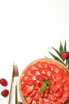 白い背景の上のイチゴのタルトとおいしい料理のコンセプトです。