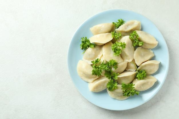 Концепция вкусной еды с варениками или варениками на белом текстурированном столе