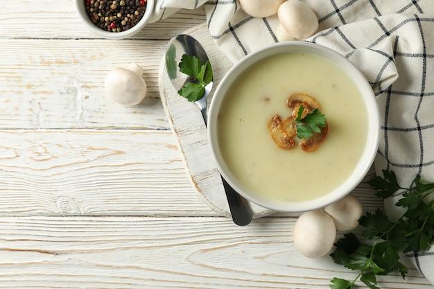 Концепция вкусного обеда с миской грибного супа на белом деревянном
