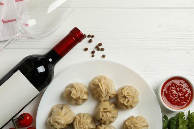 Концепция вкусного обеда с тарелкой хинкали на белом деревянном фоне