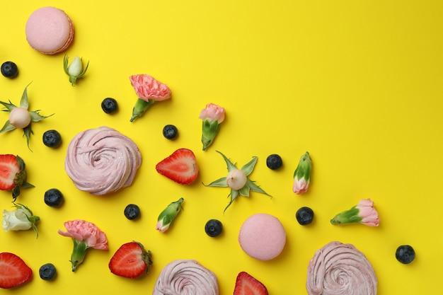 노란색 배경에 맛있는 마카롱과 마쉬 멜로우의 개념