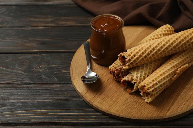Концепция вкусной еды с вафельными трубочками со сгущенным молоком на деревянных фоне