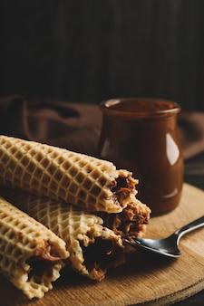 Концепция вкусной еды с вафельными трубочками со сгущенным молоком на деревянных