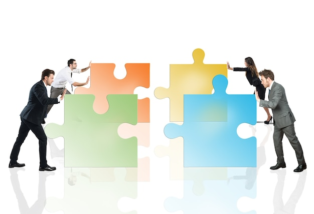チームワークとパートナーシップの概念。パズルのピースを押すビジネスマンは一緒にフィットします。