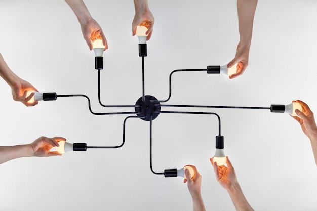チームワークの概念、または天井照明のledランプを交換する際の統一された行動の例に関する共通の目的