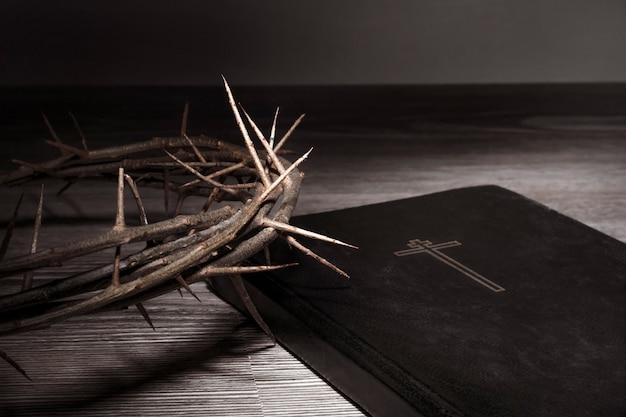 성 주간의 개념입니다. 가혹한 빛에서 가시 면류관과 성경이 테이블 위에 놓여 있습니다. 고 대비.