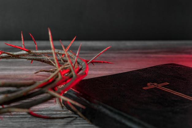 聖週間のコンセプト。赤い光の中のいばらの冠と聖書がテーブルの上にあります。
