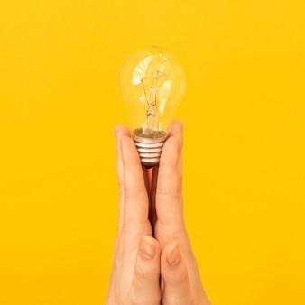 새로운 아이디어의 개념, 주황색 노란색 배경에 손을 클로즈업한 전구, 격리된 사진