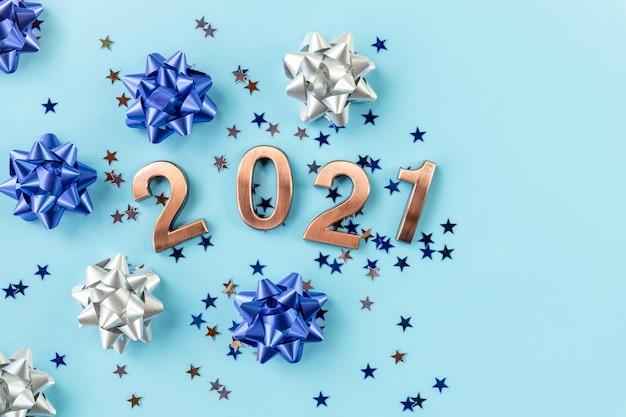 2021年の新年のコンセプト。金の数字は青い表面に立っています